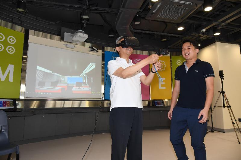 公務員事務局局長羅智光(左)今日(七月二十四日)到訪東區時參觀了香港專業教育學院(柴灣)。圖示羅智光試用學生研發的虛擬實境技術系統。