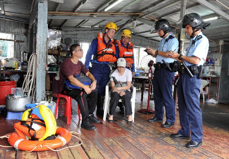 離島民政事務處今日(七月二十四日)在大澳舉行跨部門水浸模擬救援及疏散演練。圖示演練中被困居民致電求助後,消防處及警務處派員到場拯救。