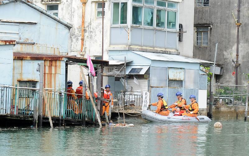 離島民政事務處今日(七月二十四日)在大澳舉行跨部門水浸模擬救援及疏散演練。圖示民安隊隊員在演練中用橡皮艇拯救被圍困的居民。