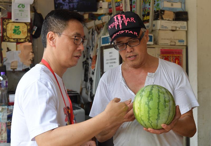 教育局局長楊潤雄(左)今日(七月二十五日)進行家訪,先到油麻地一間地區小店選購水果,趁機了解區內商店的經營情況。