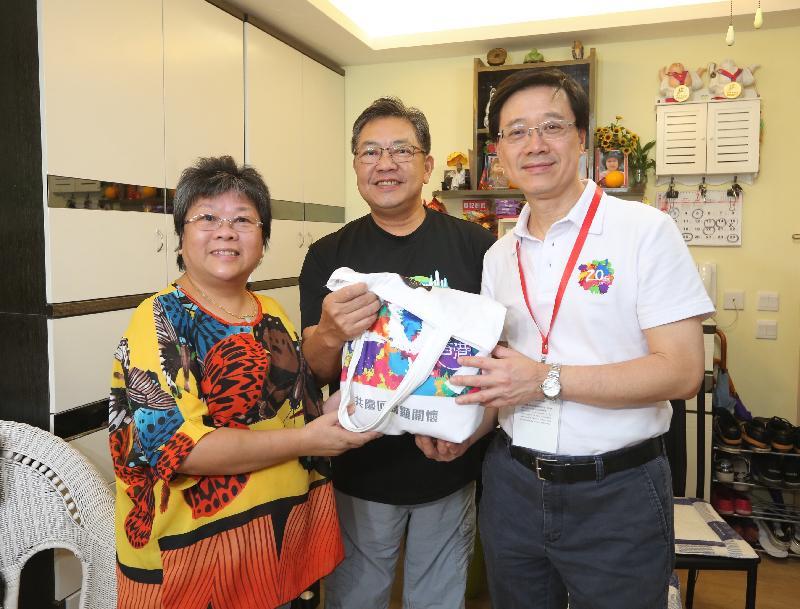 保安局局長李家超(右一)今日(七月二十六日)在欣安邨向一個家庭送上香港回歸二十周年禮物包。