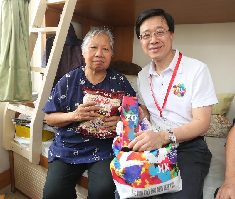保安局局長李家超(右)今日(七月二十六日)在欣安邨向長者送上香港回歸二十周年禮物包。