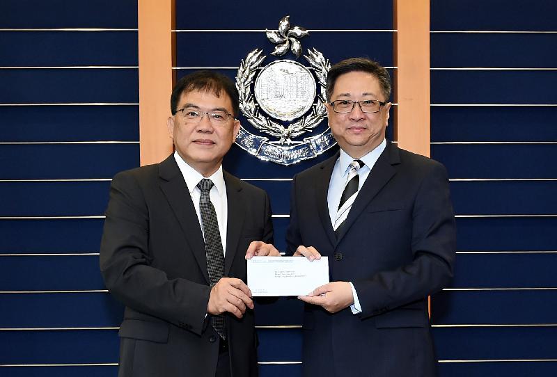 警務處處長盧偉聰(右)頒授委任狀予新任香港輔助警察隊副總監鄭文森(左)。