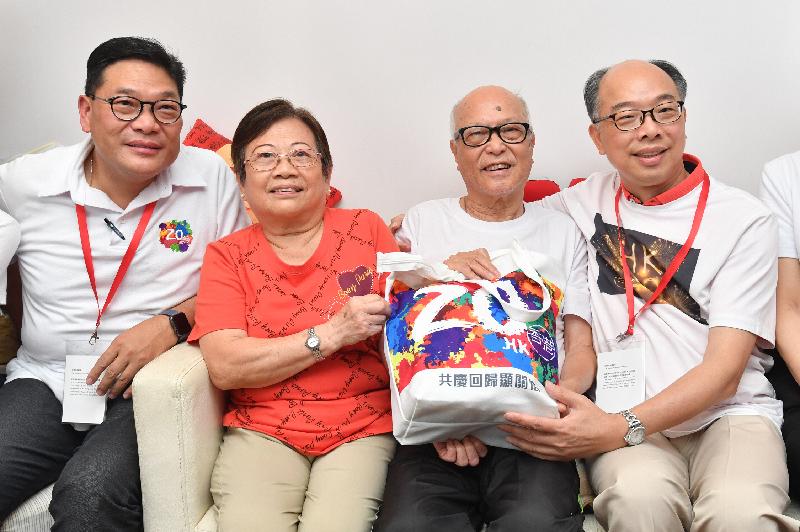 运输及房屋局局长陈帆(右)今日(七月二十八日)探访中西区一对长者夫妇,向他们送上香港回归二十周年礼物包。