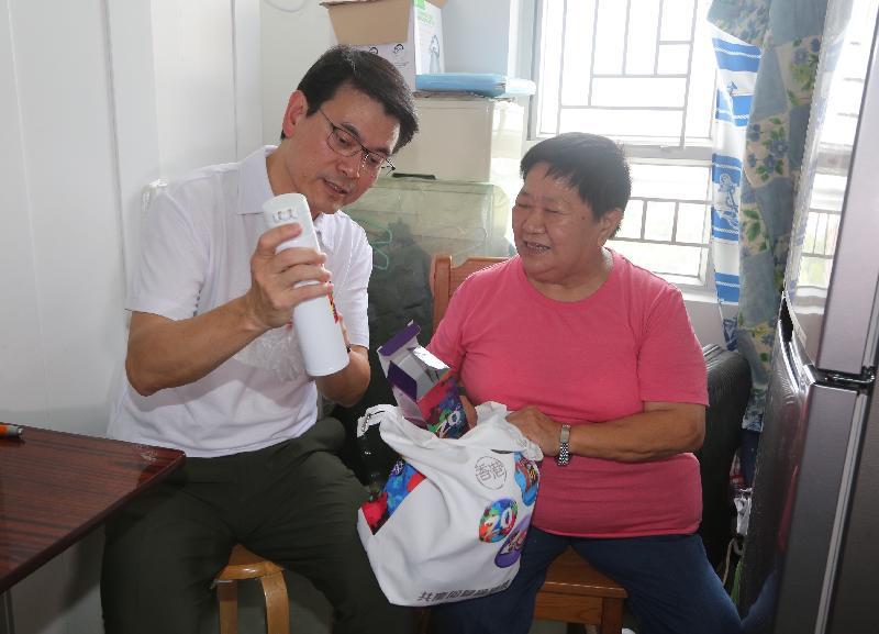 商务及经济发展局局长邱腾华(左)今日(八月一日)到访北区,探访一位居于上水祥龙围邨的长者,了解她的需要和日常生活情况,并向她派发礼物包。