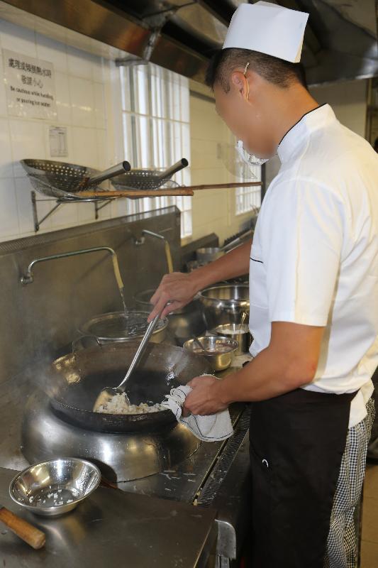 懲教署今日(八月四日)於塘福懲教所舉行「中式廚藝及酒樓服務證書課程」暨「木模板工藝課程」證書頒發典禮。圖示一名修畢「中式廚藝及酒樓服務證書課程」的在囚人士在訓練廚房示範炒飯。