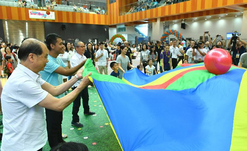 署理行政長官張建宗今日(八月六日)下午到圓洲角體育館參與由康樂及文化事務署(康文署)主辦的「全民運動日2017」活動,與市民一起體驗做運動的樂趣和好處。圖示張建宗(左一)和民政事務局局長劉江華(左三)與小朋友和家長一同參與彩虹傘遊戲。