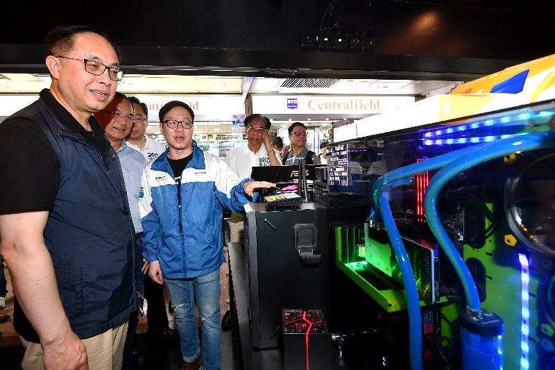 創新及科技局局長楊偉雄(左一)今日(八月六日)下午參觀深水埗區電腦主題商場,聽取店員介紹。