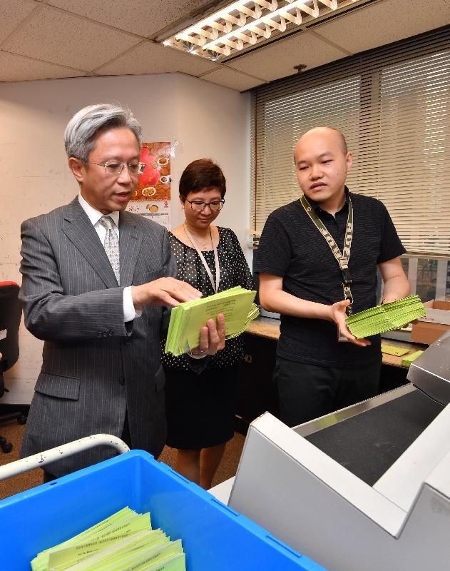 公務員事務局局長羅智光(左)今日(八月七日)參觀稅務局文件處理中心,了解員工處理報稅表的流程。