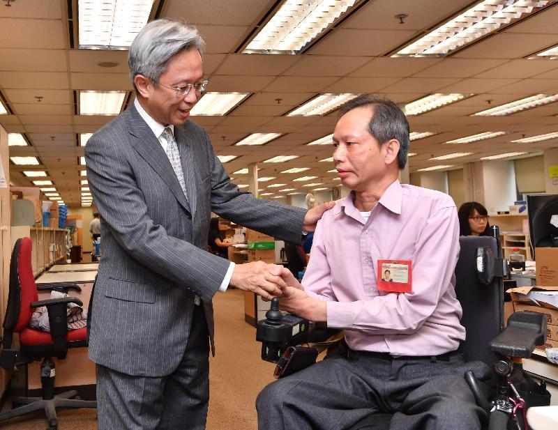 公務員事務局局長羅智光(左)今日(八月七日)在稅務局與殘疾同事交談,了解稅務局為幫助殘疾人員融入工作環境所提供的協助。