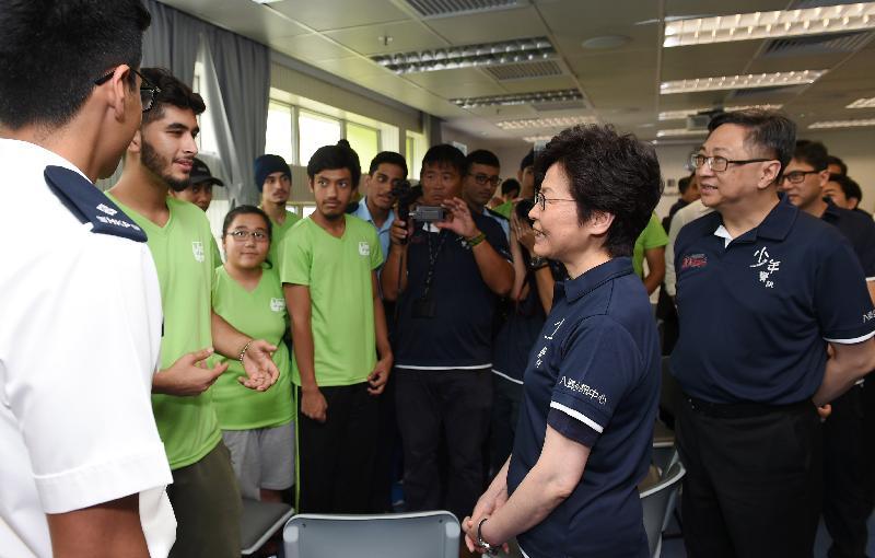 行政長官林鄭月娥(中)在少年警訊永久活動中心暨青少年綜合訓練營與非華裔的少年警訊會員談話。旁為警務處處長盧偉聰(右一)。
