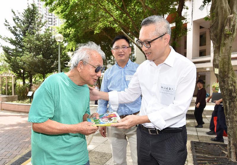 食物及衞生局副局長徐德義醫生(右)今日(八月十二日)視察天水圍區的控蚊措施,他贈送防蚊清潔包給一名天瑞邨長者。