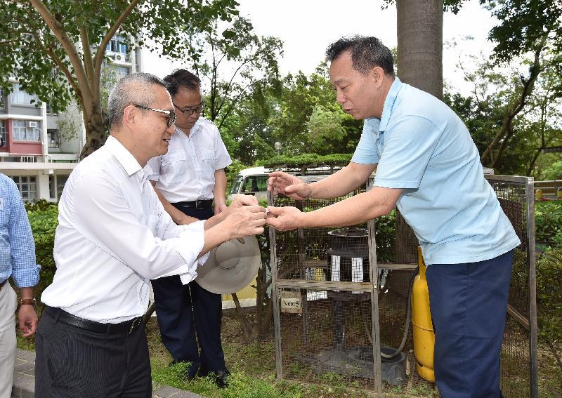 食物及衞生局副局長徐德義醫生(左)今日(八月十二日)視察天水圍區的控蚊措施。房屋署人員向他講解在屋邨設置的捕蚊器的功能。