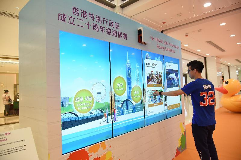 「香港特別行政區成立二十周年巡迴展覽」今日(八月十七日)起在尖沙咀海港城海運大廈展覽大堂舉行。圖示參觀展覽的市民透過電子觸控式屏幕,回顧香港過去二十年的發展和成就。