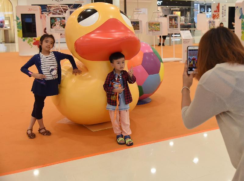 「香港特別行政區成立二十周年巡迴展覽」今日(八月十七日)起在尖沙咀海港城海運大廈展覽大堂舉行。圖示參觀展覽的市民為孩子與小黃鴨和足球立體模型拍照。