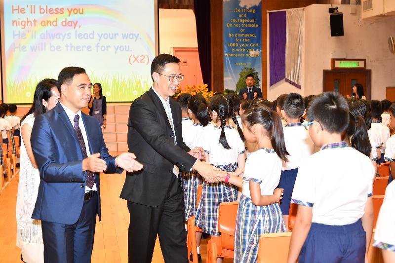 教育局局长杨润雄(左三)今日(九月一日)在基督教宣道会宣基小学开学礼上与学生握手问好。
