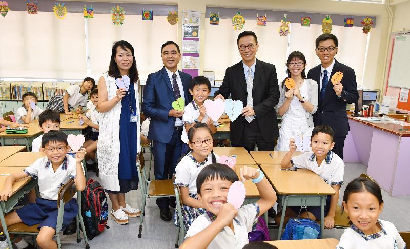 教育局局长杨润雄(后排右三)今日(九月一日)探访基督教宣道会宣基小学。图示杨润雄与老师及学生展示自制的书签。