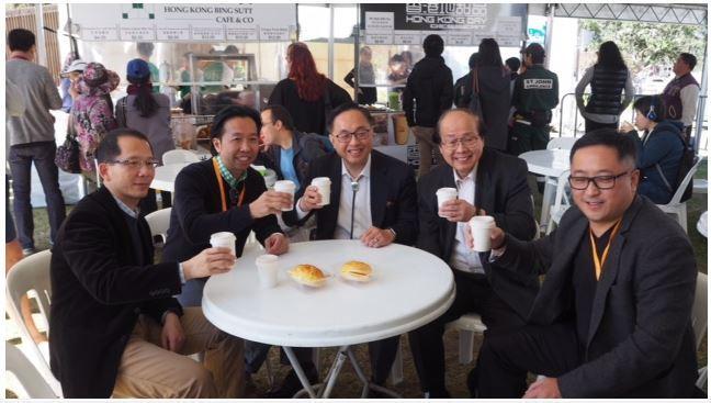 「HK20缤纷嘉年华」今日(悉尼时间九月九日)在悉尼举行。图示创新及科技局局长杨伟雄(中)在美食摊位一尝香港地道美食。