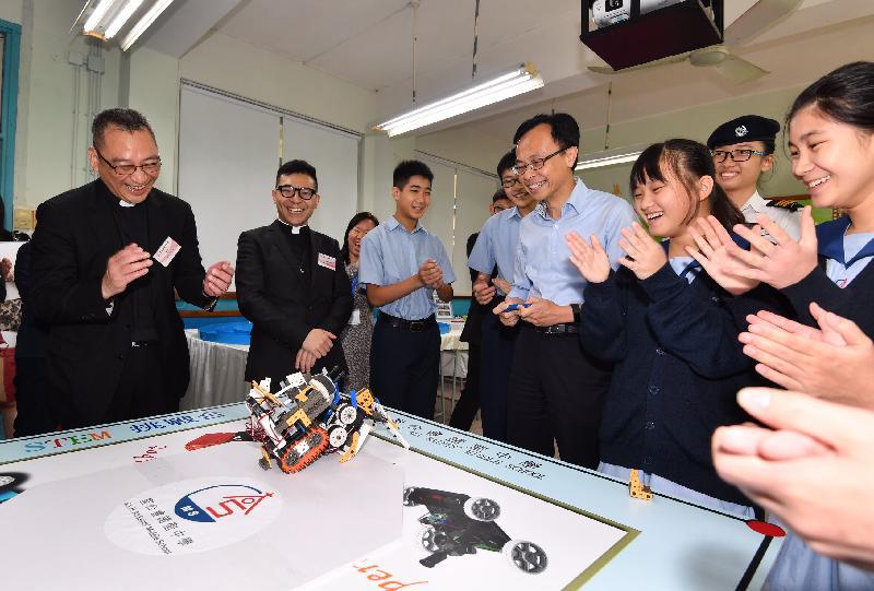 政制及內地事務局局長聶德權今日(九月十五日)到訪聖公會諸聖中學的STEM工作室,聆聽學生講解和示範他們設計的項目。圖示聶德權(右四)操作由學生研發的機械人。
