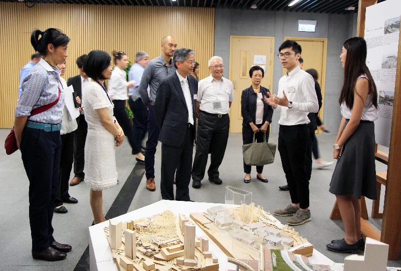 """The Greening, Landscape and Tree Management Section of the Development Bureau organised an exhibition held under """"Liveability by Design"""" Studio Initiative. Photo shows the Permanent Secretary for the Development (Works), Mr Hon Chi-keung (centre) and the Deputy Secretary for Development (Works), Ms Joey Lam (second left), being briefed by the participating student on his work concept. Looking on is the Head of Greening, Landscape and Tree Management Section of the Development Bureau, Ms Deborah Kuh (first left)."""