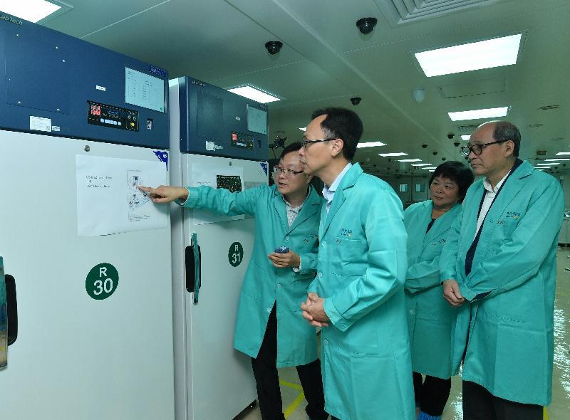政制及內地事務局局長聶德權今日(九月二十七日)到訪大埔區,並參觀香港華大基因科技服務有限公司,聽取公司代表介紹基因科技發展。圖示聶德權(左二)參觀公司的設施,了解基因測序儀器的運作。