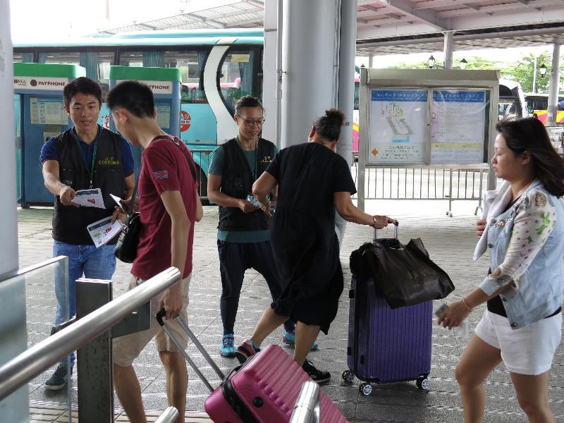 香港海關今日(九月二十九日)展開名為「神盾」的巡查行動,加強於「國慶黃金周」期間對旅客的消費保障。圖示海關人員在過境巴士站提醒訪港旅客精明消費。