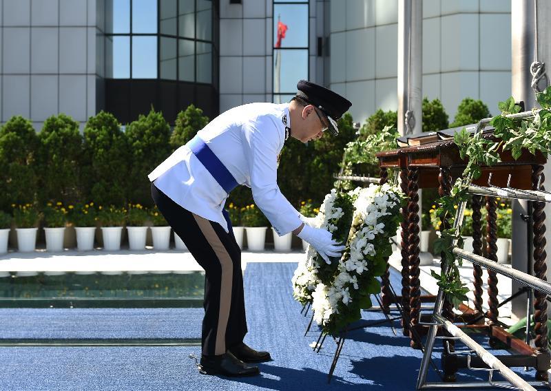 警務處處長盧偉聰於刻有殉職人員姓名的紀念冊前獻上花圈。