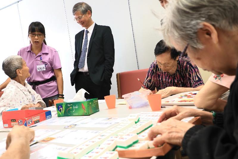 勞工及福利局局長羅致光博士今早(十月十八日)到訪循道衛理楊震社會服務處健憶長者認知訓練中心。圖示羅致光博士(左三)觀察長者進行個人訓練活動。