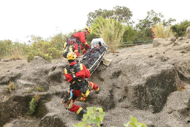 消防處人員在今日(十月十九日)舉行的跨部門山火暨攀山拯救行動演習中模擬拯救一名傷者。