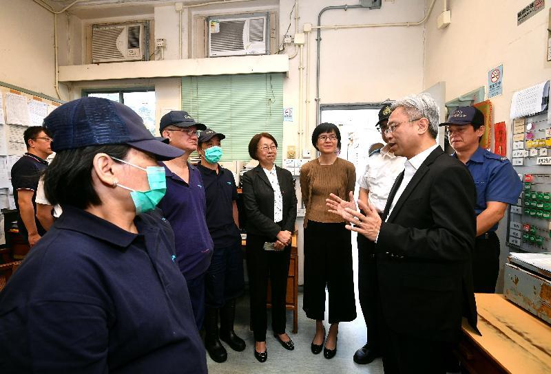公務員事務局局長羅智光(前右)今日(十月二十四日)到訪食物環境衞生署,其間聽取屍體處理隊人員講解他們的工作。
