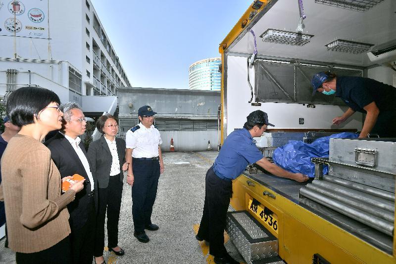 公務員事務局局長羅智光(左二)今日(十月二十四日)到訪食物環境衞生署,其間聽取屍體處理隊人員講解他們的工作。