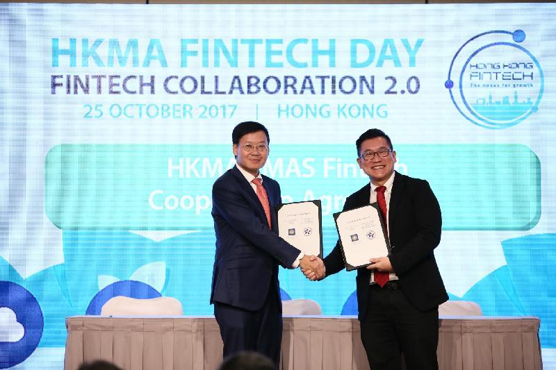 香港金融管理局(金管局)助理總裁李樹培(左)與新加坡金融管理局金融中心發展部主管Roy Teo(右)今日(十月二十五日)在金管局舉辦的「金融科技日」上,交換由兩地金管局負責人簽署的《合作協議》。