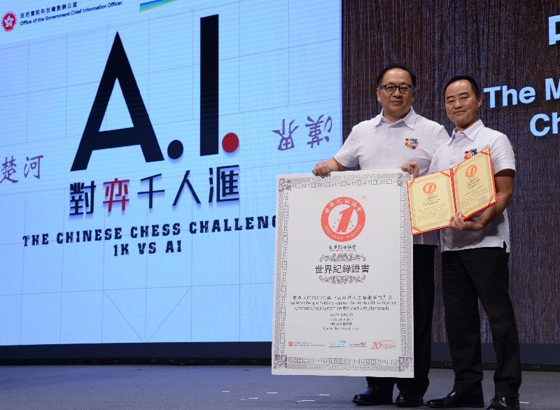 世界纪录协会确认今日(十月二十七日)参与「AI对弈千人汇」挑战日的1 140名中、小学生创下「最多人同时同地与中国象棋人工智能系统对弈」的世界纪录。助理政府资讯科技总监(产业发展)黄志光(右)和香港数码港管理有限公司公众使命总监湛家扬博士(左)代表接受证书。