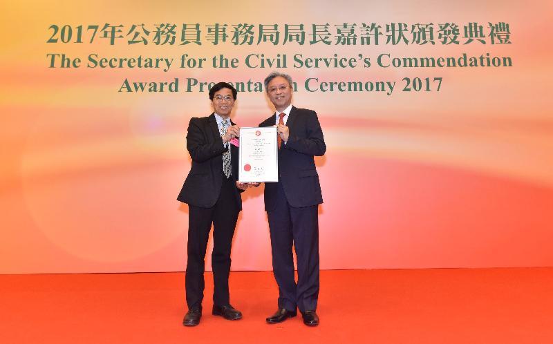 公務員事務局局長羅智光(右)在今日(十一月二日)舉行的典禮上頒發嘉許狀予一名表現優秀的公務員。