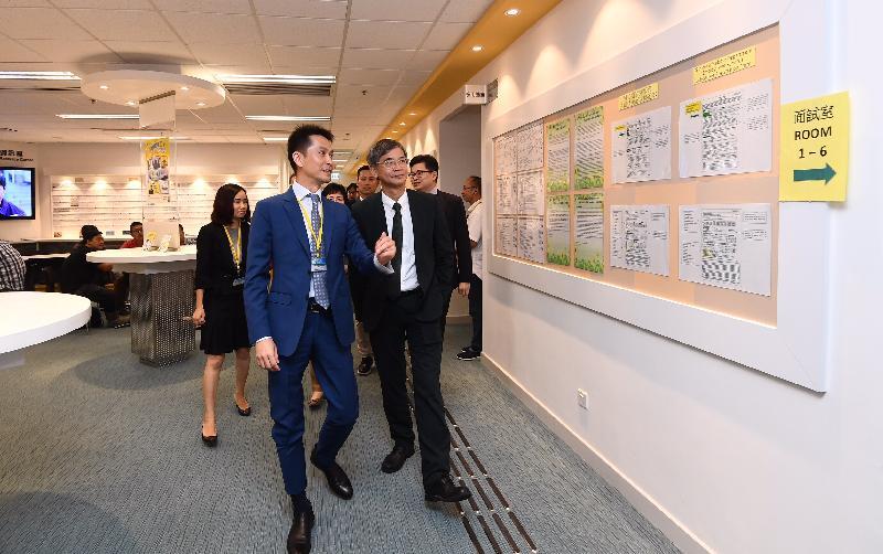 勞工及福利局局長羅致光博士今日(十一月七日)到訪位於九龍灣的勞工處建造業招聘中心。圖示羅致光博士(右)聽取中心職員介紹中心的多元化服務。
