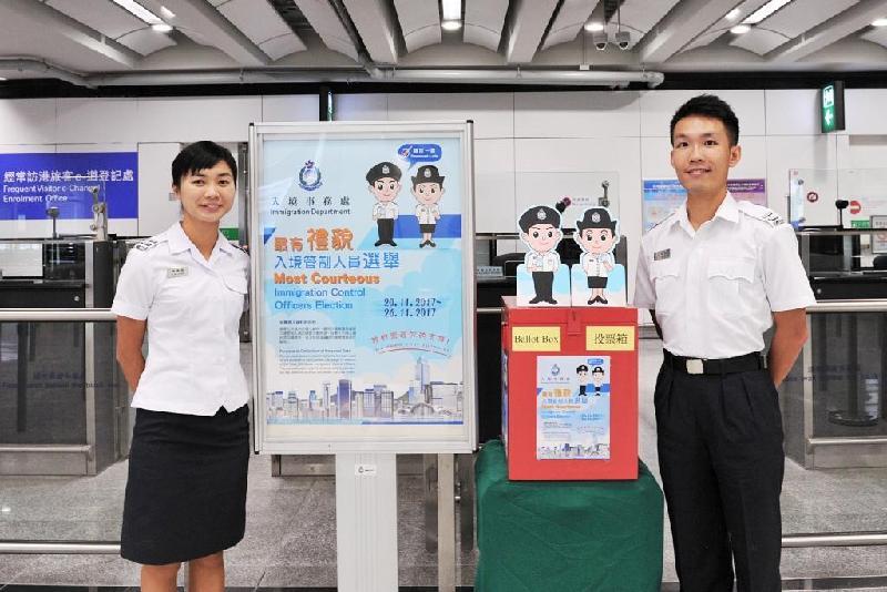 入境事務處今日(十一月十日)呼籲旅客參與投票,支持該處一年一度的禮貌運動。圖示入境管制人員展示「最有禮貌入境管制人員選舉」投票箱及宣傳海報。
