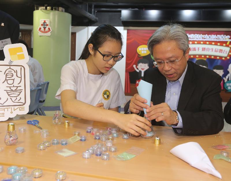 公務員事務局局長羅智光今日(十一月十五日)到訪東華三院賽馬會大角咀綜合服務中心。圖示羅智光(右)在中心製作創意手工藝品。