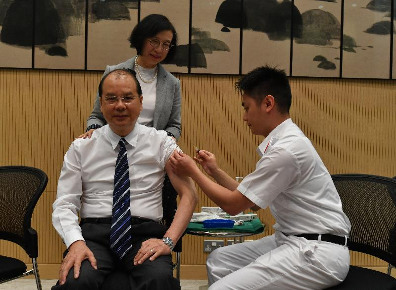 The Chief Secretary for Administration, Mr Matthew Cheung Kin-chung (front row, left), today (November 15) receives seasonal influenza vaccination by registered nurse Mr Leung Sin-fai (front row, right). Looking on is the Secretary for Food and Health, Professor Sophia Chan (back).