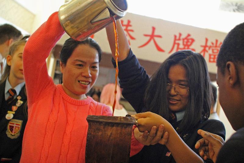 香港駐倫敦經濟貿易辦事處於十一月十五日(倫敦時間)在倫敦舉辦為期十天的「探索香港非物質文化遺產的旅程」展覽。圖示製作奶茶大師莫佩玲(左一)在展覽上教授倫敦當地中學學生如何製作奶茶。