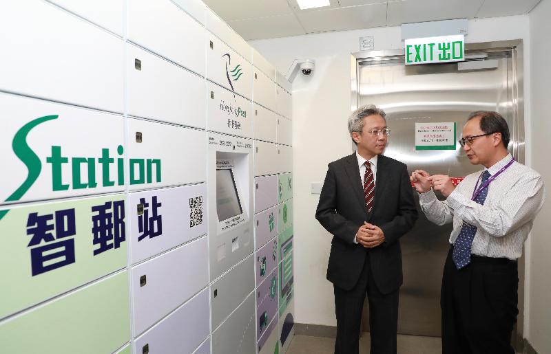 公務員事務局局長羅智光今日(十二月五日)到訪香港郵政。圖示羅智光(左)聆聽部門同事講解「智郵站」自助領件櫃的運作。