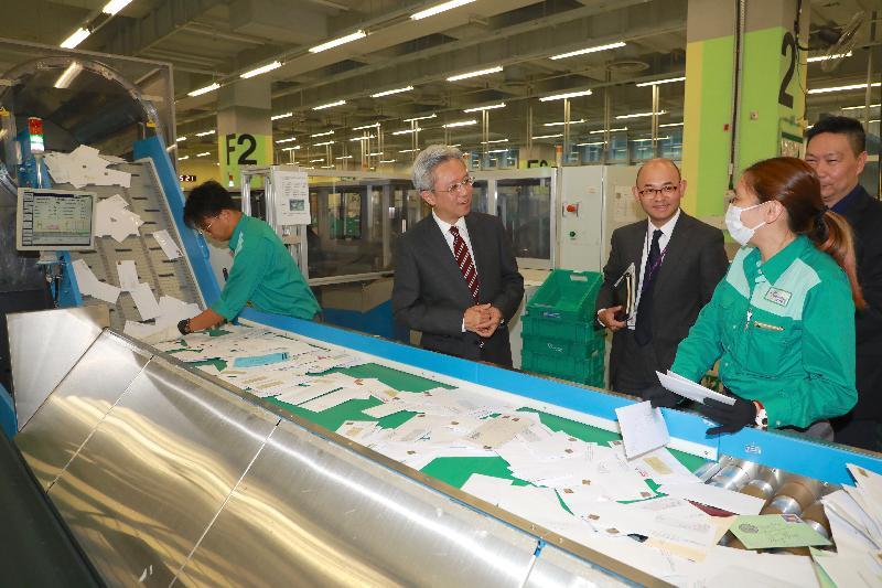 公務員事務局局長羅智光今日(十二月五日)到訪香港郵政。圖示羅智光(左二)了解自動化分信戳郵機如何加快處理信件的流程。