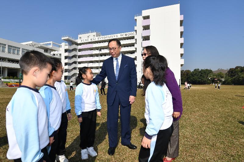 創新及科技局局長楊偉雄(左五)今日(十二月十一日)在鳳溪創新小學草地球場與學生交談。