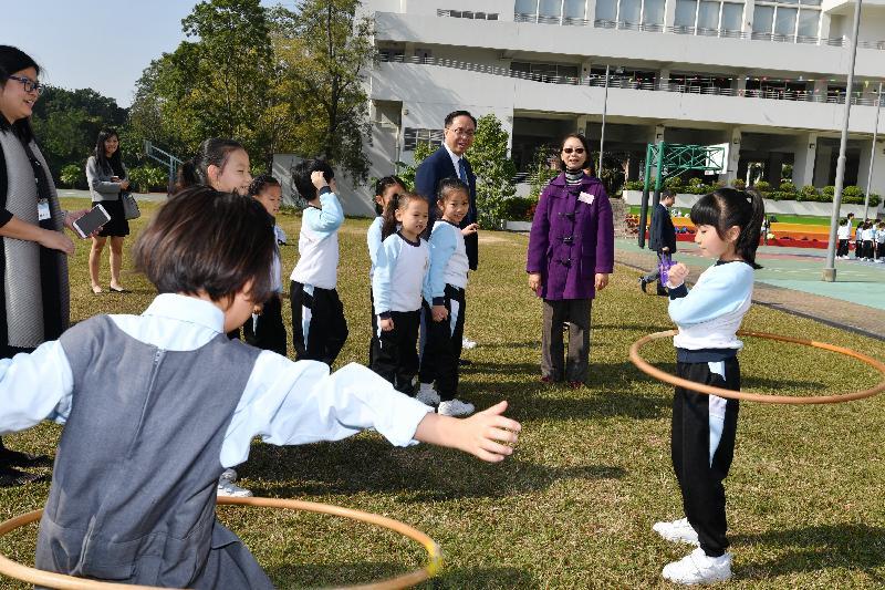 創新及科技局局長楊偉雄(後排右二)今日(十二月十一日)在鳳溪創新小學校長李淑賢(後排右一)陪同下,觀看學生在草地球場進行活動。