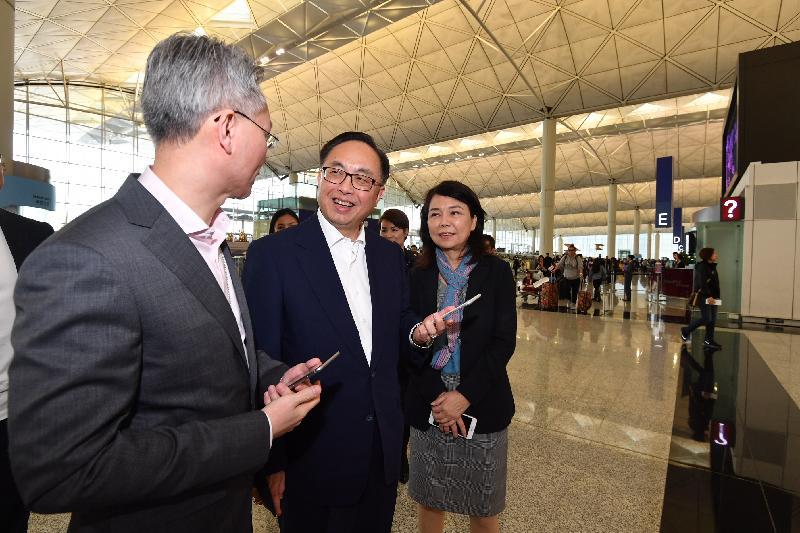 創新及科技局局長楊偉雄(中)今日(十二月十四日)在香港國際機場試用「我的航班」應用程式的擴增實境路線搜尋。旁為香港機場管理局機場運行副總監張李佳蕙(右)。