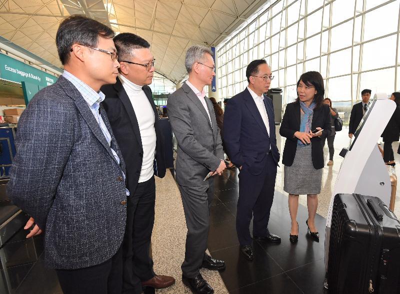 創新及科技局局長楊偉雄(右二)今日(十二月十四日)在香港國際機場聽取香港機場管理局機場運行副總監張李佳蕙(右一)介紹自助登記服務。