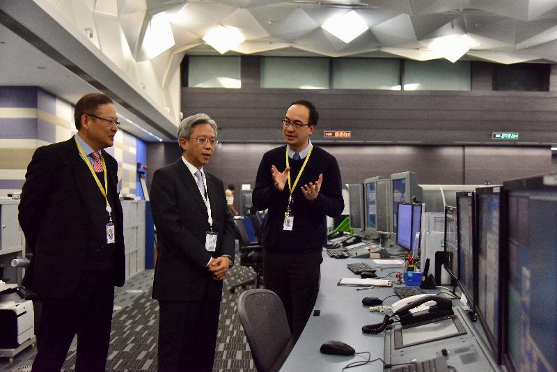 公務員事務局局長羅智光今日(一月十日)到訪民航處。圖示羅智光(中)聆聽部門同事介紹新航空交通管理系統的主要特點和運作情況,旁為民航處處長李天柱(左)。