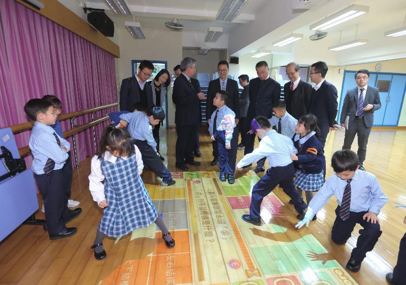 教育局局長楊潤雄(右五)今日(一月十七日)到訪觀塘聖愛德華天主教小學,並觀看同學在互動地板上進行遊戲學習。