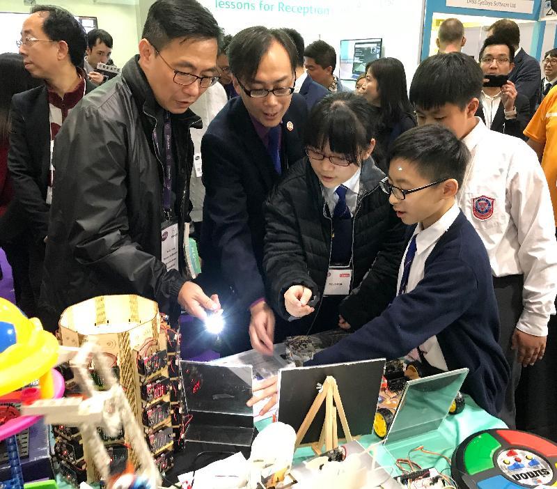 教育局局長楊潤雄(左)昨日(倫敦時間一月二十四日)在倫敦參觀英國教育科技展BETT Show,觀看香港學生示範他們作品的用途。