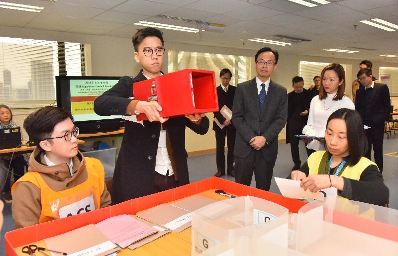 政制及內地事務局局長聶德權(左三)今日(一月三十日)到訪選舉事務處,了解點票工作的流程。