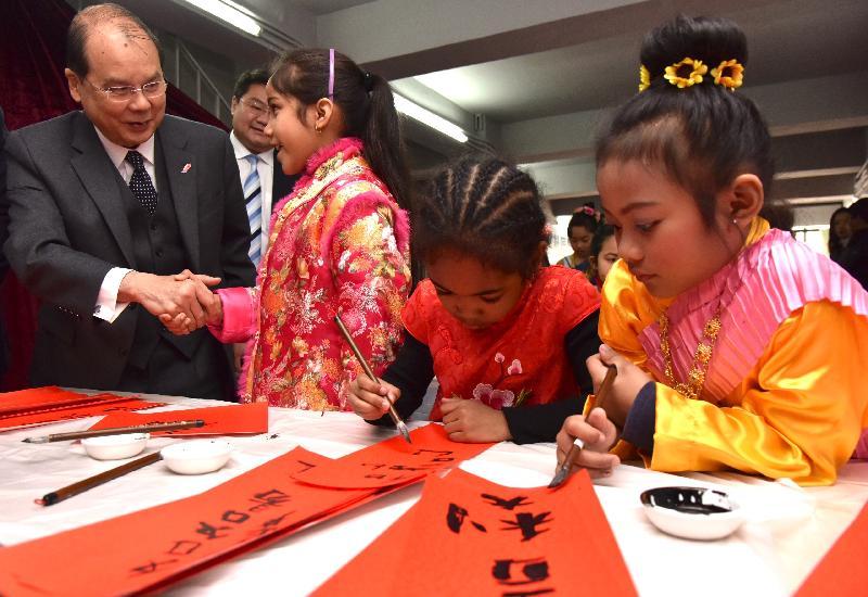政務司司長張建宗今日(二月十四日)到訪九龍樂善堂共享服務間並觀看少數族裔學生寫揮春。圖示張建宗(左一)與一名少數族裔學生交談。